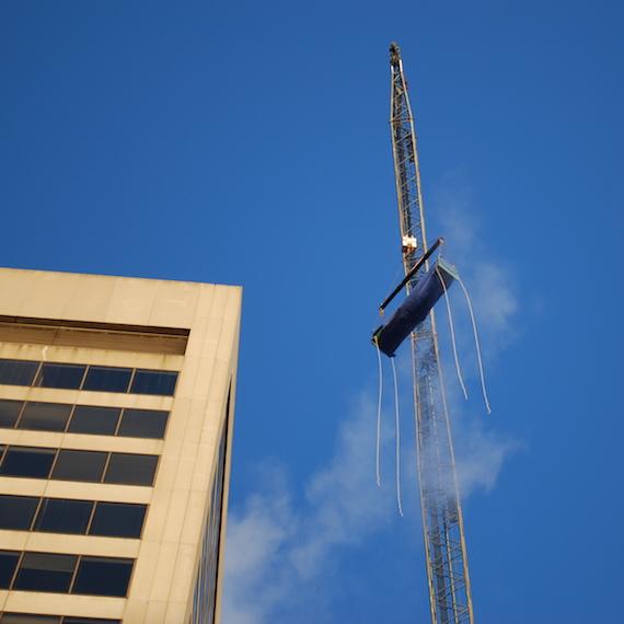 Grue soulevant des équipements mécaniques sur le toit d'une tour à bureaux