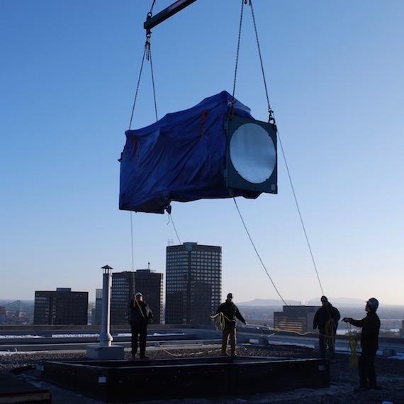 Grue déposant des équipements mécaniques sur le toit d'une tour à bureaux